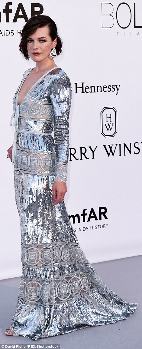 Eye-catching: The Resident Evil star, 40, wasn't afraid to stand out from the crowd in a floor-sweeping gown that was adorned with an array of sequin embellishments and semi-sheer panels that were daringly located along the bust and waist