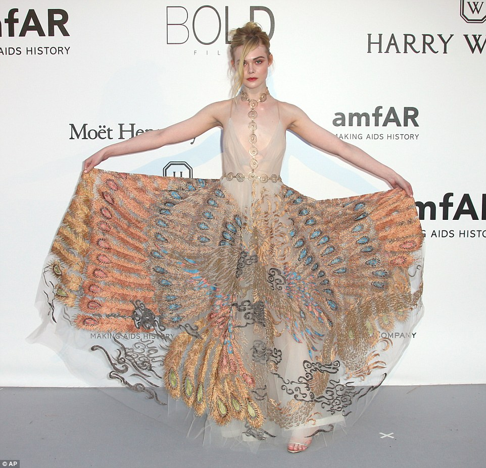 To be admired: Elle Fanning showcased her peacock inspired number in all of its glory as she lifted up the skirt of the semi-sheer desin