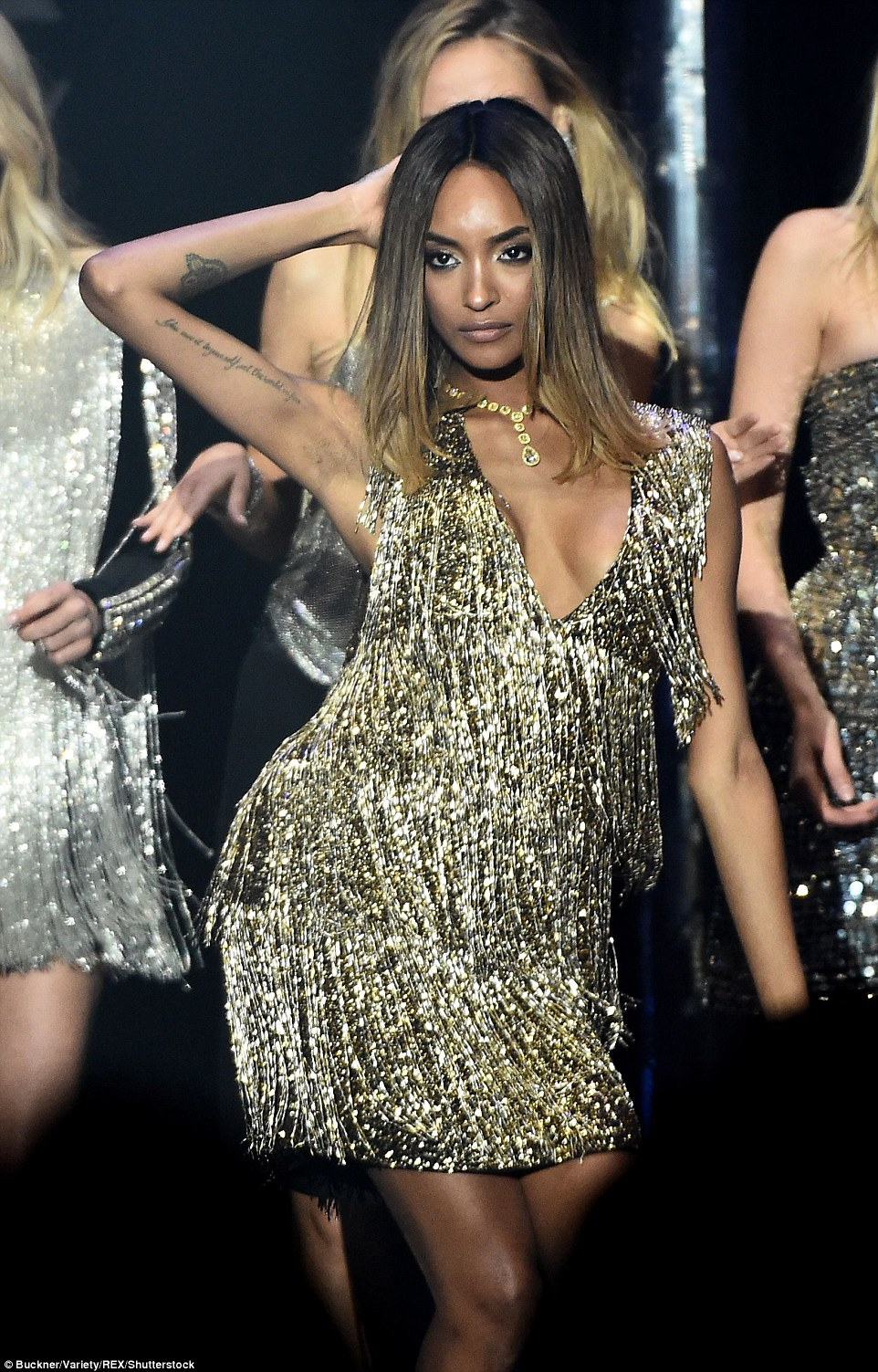 Doing her thing:Jourdan Dunn led the models after Bella Hadid as she slipped into a stunning gold fringed gown with a plunging neck and bare sleeves, which acted to show off her heavily inked skin