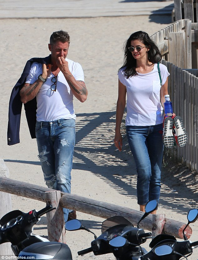 Relaxed: Lapo was dressed down in a simple white T-shirt and distressed jeans, slinging a jacket over one shoulder as he hit the beach