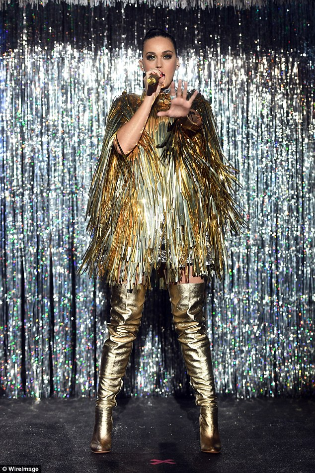 Golden girl: Katy changed into a shredded golden cape and over-the-knee boots for her performance