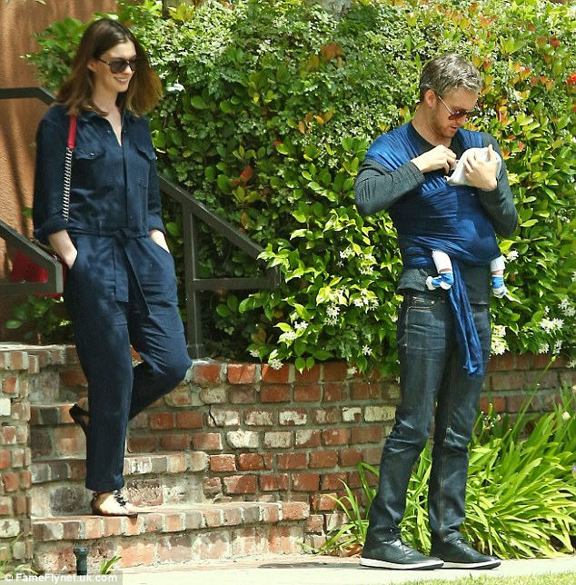 In good spirits: Anne showed off a big smile as she watched husband Adam doting on their little bundle of joy