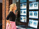 E027NB woman looking at homes for sale at an estate agents office in Essex, UK