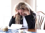 A stock photo of a woman worried about bills and debt.   CNB0FM