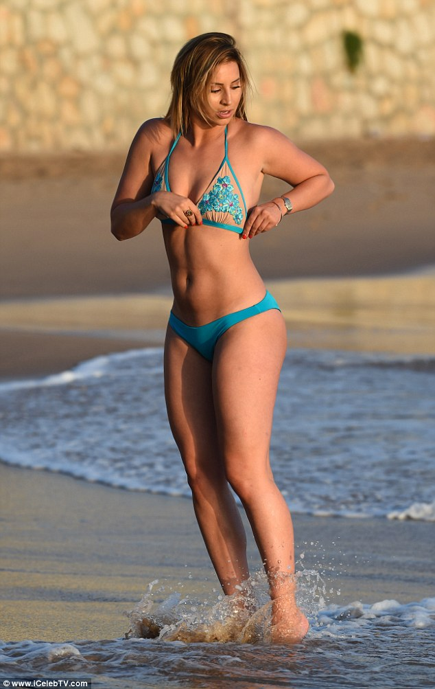 Avoiding a wardrobe fail? The former TOWIE star adjusts her swimsuit as she risks a slip-up