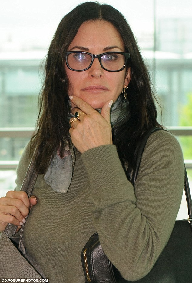 Showing it off: Courteney discreetly displayed her engagement ring as she touched down at London's Heathrow Airport last week