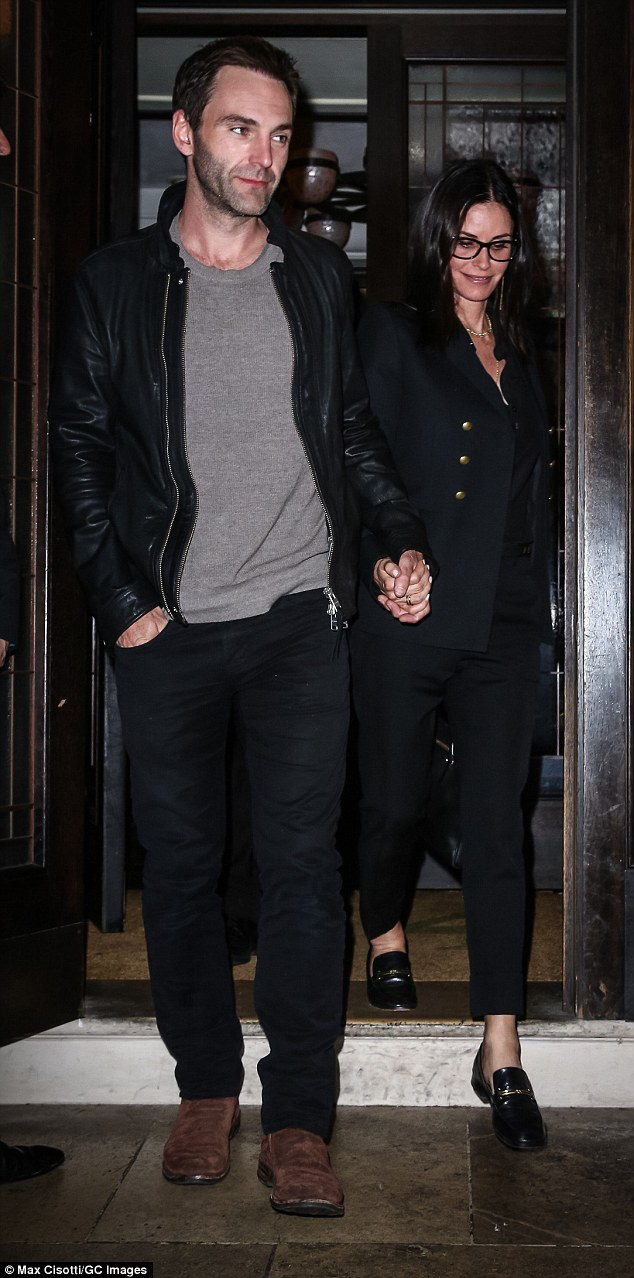Looking cool: Courteney's handsome other half complemented her look with a casual grey knit sweater, leather jacket, blue jeans and brown shoes