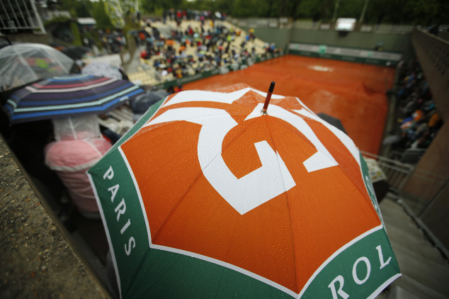 Spectators wait at covered tennis courts for the start of rain delayed first round matches of the French Open tennis tournament against at Roland Garros stad...