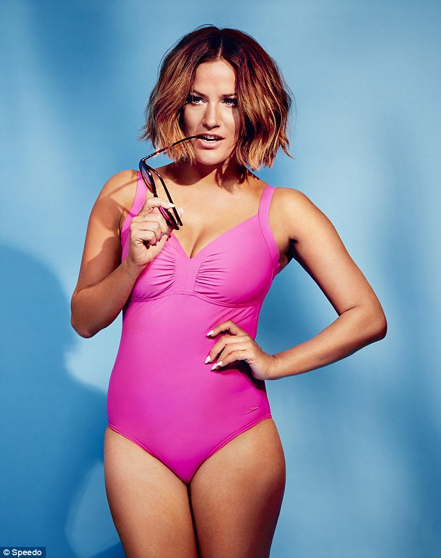 Pretty in pink: The brunette beauty show off her playful side in another shot which see her biting on her sunglasses while sporting a plunging pink swimsuit