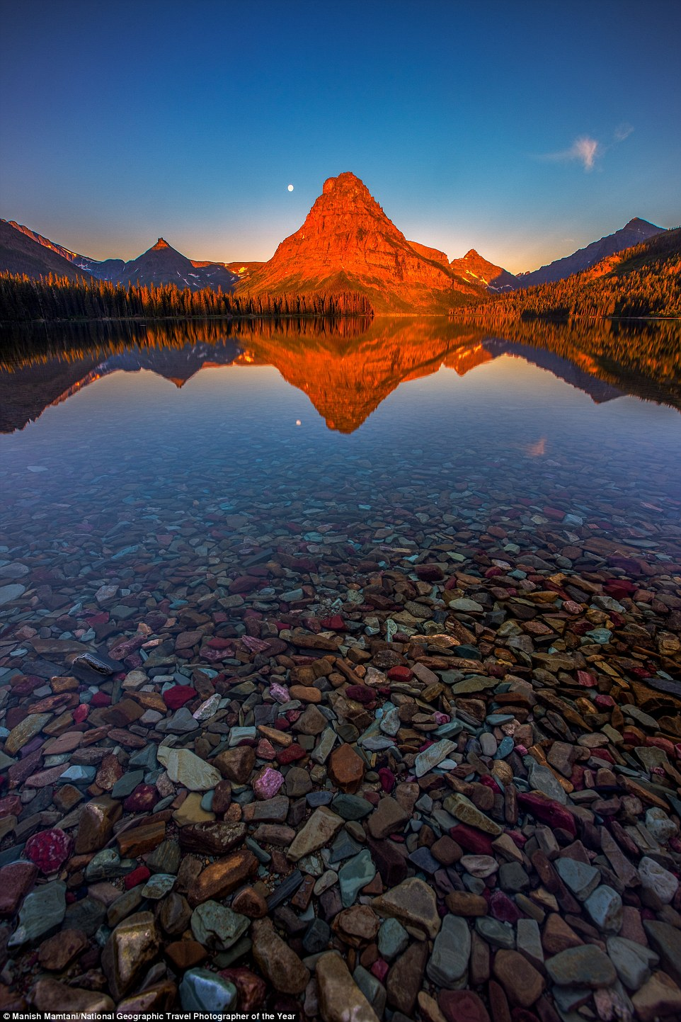 Manish Mamtani drove one early morning from St. Mary's Lodge to see the sunrise at Two Medicine lake in Glacier National Park in Montana. There were no clouds but the lake water was so calm it created a perfect reflection of the red light kissing the Sinopah Mountain. As there was no wind in the morning, the colourful rocks in the foreground were visible