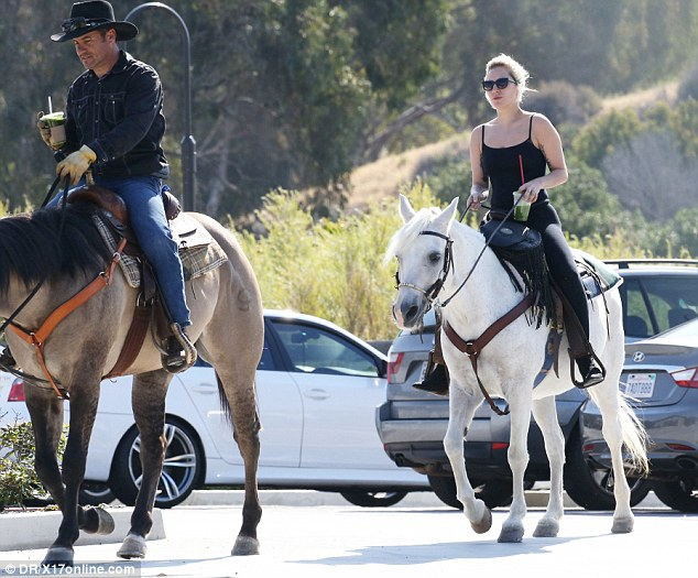 He sure looks like a country boy: The Poker Face hit maker did not appear to be alone as there was a male on a brown horse next to her