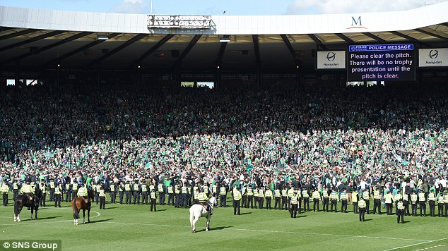 Police attempt to push back the Hibernian fans who were attempting to make their way down to the pitch