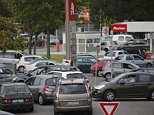 Cars wait to get gas at a petrol station at a supermarket in Saint-Sebastien-sur-Loire near Nantes, France, May 21, 2016 as Total has halted output at some units of three of its refineries in France due to protests over proposed labour law reform that have prompted a blockade of oil depots and petrol stations.   REUTERS/Stephane Mahe ATTENTION EDITORS FRENCH LAW REQUIRES THAT VEHICLE REGISTRATION PLATES ARE MASKED IN PUBLICATIONS WITHIN FRANCE