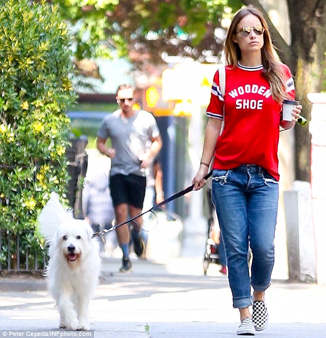 Olivia Wilde covered up her growing baby bump while walking her dog on Monday in New York City.