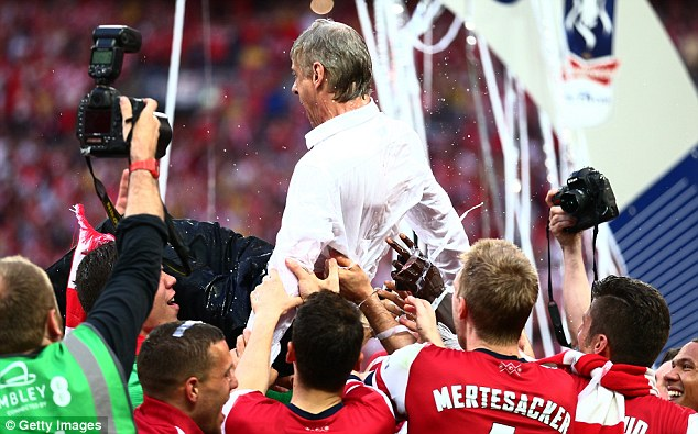 Shower time: Wenger, visibly soaked, celebrates victory with his players after beating Hull City at Wembley