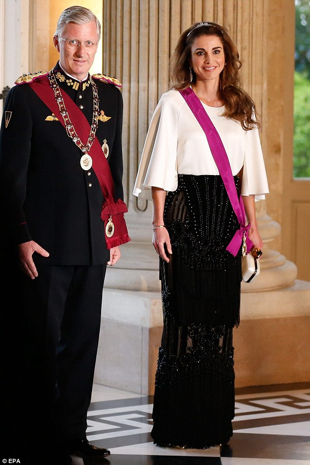 Queen Rania poses for a photograph with King Philippe of Belgium. She wore a silk white shirt with flared sleeves tucked into the waist, and dripping diamond earrings