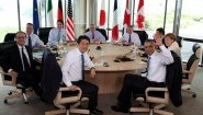 Die Staats- und Regierungschef der G7-Staaten sitzen gemeinsam an einem runden Tisch, Obama winkt in die Kamera. (dpa)