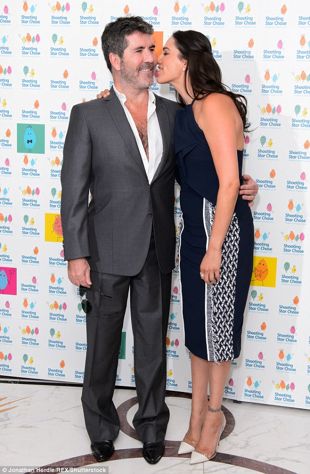 Cosy: Simon Cowell and Lauren Silverman couldn't seem to keep their hands off each other as they put on a loved-up display at the Shooting Star Chase Children's Hospice afternoon tea in London on Friday