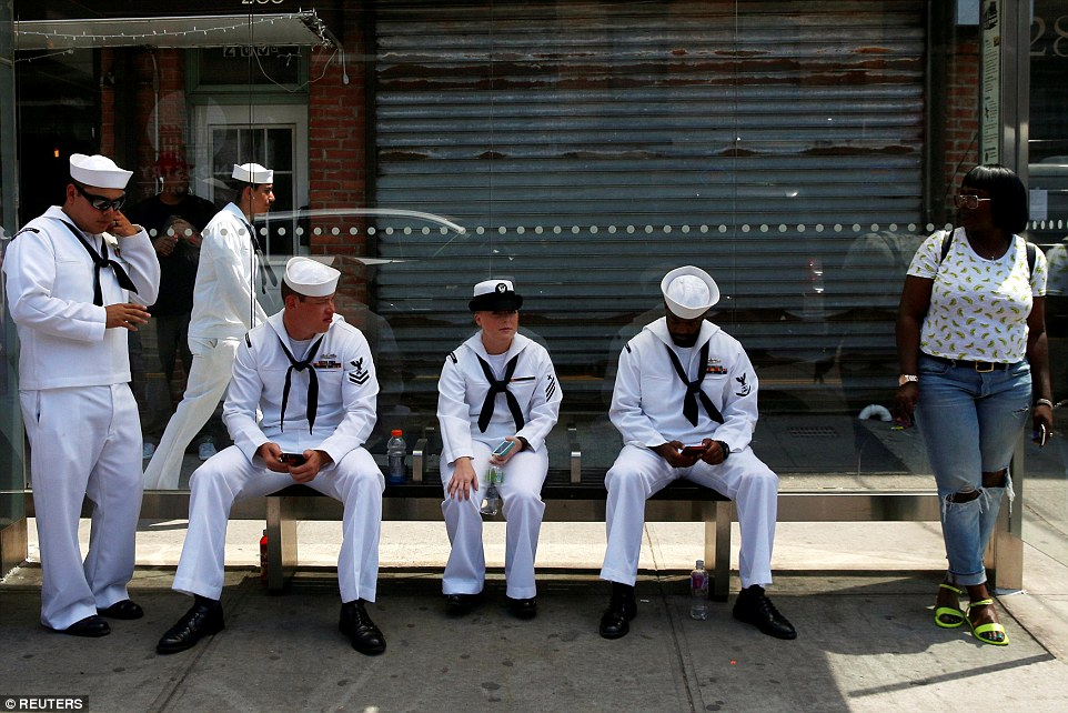 A handful of the 4,500 sailors in New York were seen waiting for a bus in Brooklyn as they headed into town for the event