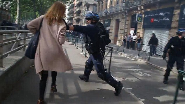 The uniformed officer forcefully lunges at her as she passes