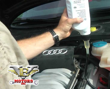 photo of mechanic giving an oil change on an audi with VE Motors logo and phone number