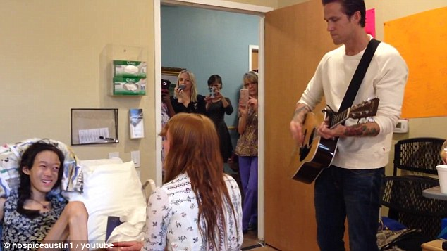 Making her day: Florence Welch held the hand of the 15-year-old patient at Hospice Austin's Christopher House on Friday as she and the girl sang Shake It Out and Dog Days Are Over while backed by the frontwoman's bandmate Rob Ackroyd on guitar