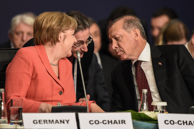 "German Chancellor Angela Merkel, left, talks through an interpreter to Turkey's President Recep Tayyip Erdogan, right, during a roundtable meeting on ""Politi..."