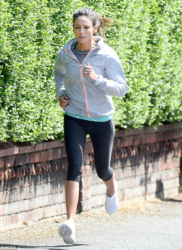 On the go: Michelle was later spotted running on location in a pair of cropped leggings and hoodie