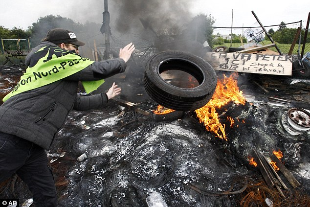 CGT union members burn tyres preventing access to a fuel depot in Douchy-les-Mines, northern France, that has led to supplies failing to reach gas stations