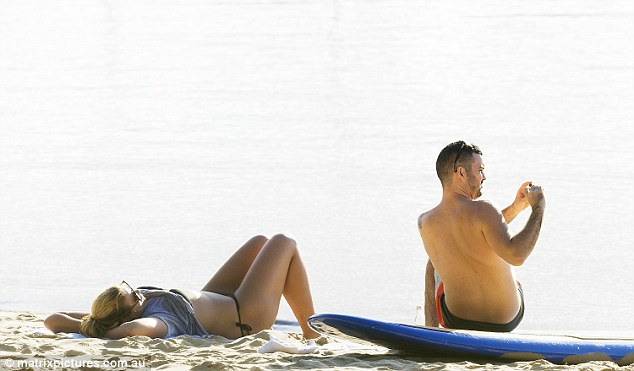 Beach babe: Flaunting her curves, the beauty looked tanned as she relaxed