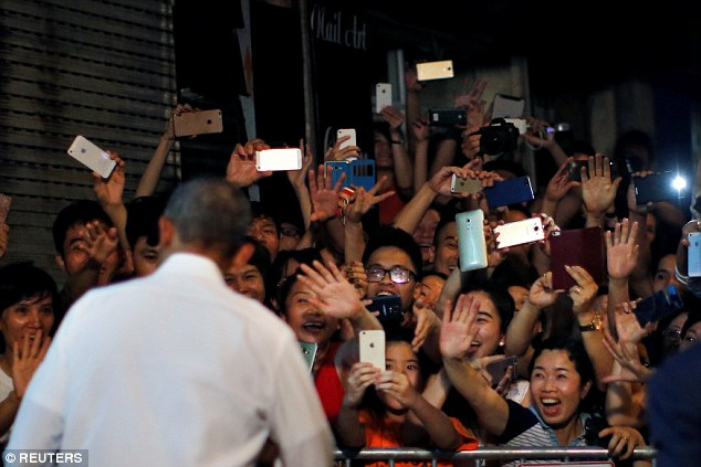 Rock star president: Local residents hoped to snap a picture as  Obama left his evening meal with  Bourdain