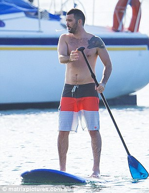 Her man showed off his tattoos as he paddled around the water