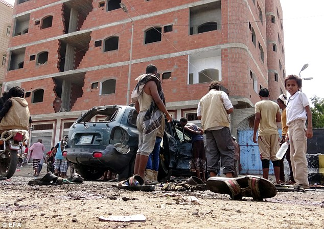 Yemenis inspect the site of a suicide bombing targeting a gathering of young men seeking to join the army in the southern port city of Aden, Yemen