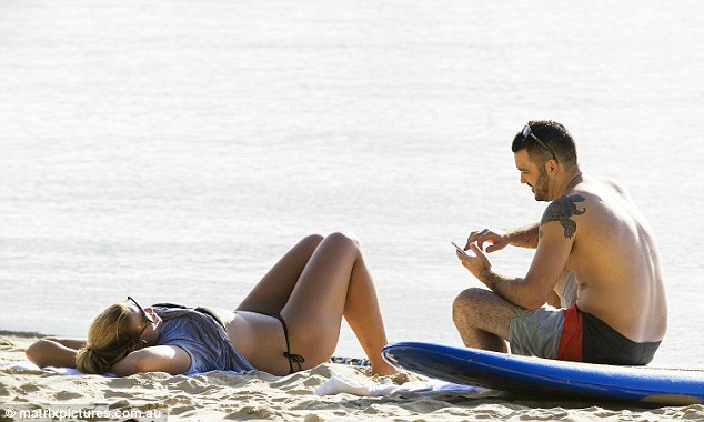 Enjoying the view:The pair perched themselves on the sand for the day, sitting on beach towels close to one another