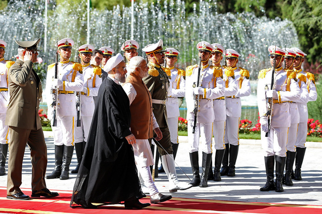 Indian Prime Minister Narendra Modi, center, walks with Iranian President Hassan Rouhani during a weloming ceremony at the Saadabad Palace in Tehran, Iran, M...