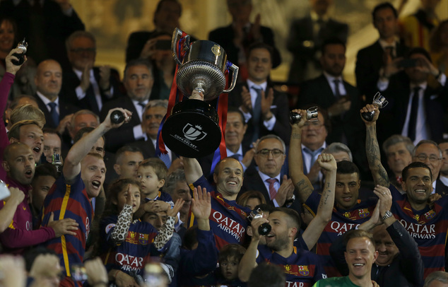 Barcelona's Andres Iniesta lift the trophy with team mates as they celebrate after winning the final of the Copa del Rey soccer match between FC Barcelona an...