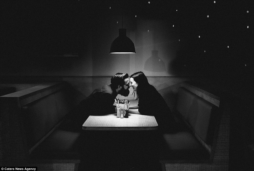 A monochrome image by Matilda Delves shows a couple sharing a cute moment in the booth of a cafe
