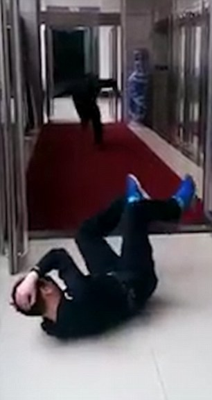 As his co-worker starts walking down the corridor towards him, he collapses dramatically as a deafening bang is heard