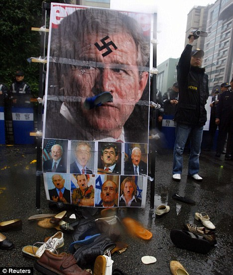 Protest: Activists throw shoes at a photo of Mr Bush during a Taiwan protest against Israeli attacks on Gaza. The US's international reputation has suffered during the Bush years