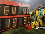 Jamaica's Usain Bolt poses next to a scoreboard after setting a new world record as he wins the gold in the men's 200-meter final during the athletics competitions in the National Stadium  at the Beijing 2008 Olympics in Beijing, Wednesday, Aug. 20, 2008. (AP Photo/David J. Phillip)