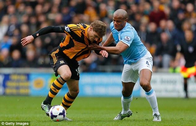 Last man standing: Kompany grabs Nikica Jelavic's shirt as the Hull striker bore down on goal