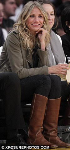 Low key: The star wore a beige jacket, jeans and tan coloured boots as she sat in her front row seats