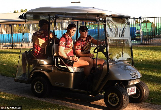 Queensland halfback Cooper Cronk is driven away for medical checks after rolling his ankle during a training session at Sanctuary Cove on the Gold Coast on Friday