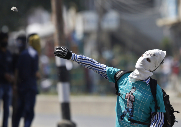 A masked Kashmiri Muslim protester throws a stone at Indian paramilitary soldiers during a protest in Srinagar, India, Friday, May. 27, 2016. Anti-India sepa...