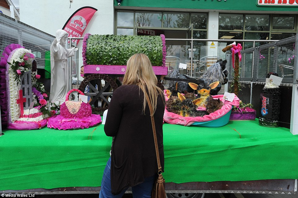A mourner at Mrs Marshall's funeral surveys the array of floral tributes, including one of a group of Yorkshire Terriers in a basket