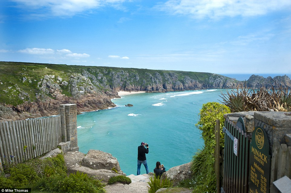 Spectacular: A visitor takes a photograph today at one of Britain's most stunning beaches - Porthcurno in Cornwall