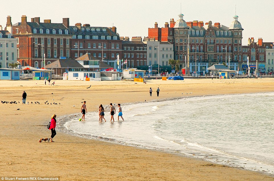 Going for a dip: A group of teenagers enjoy a paddle in the afternoon sunshine on Weymouth beach in Dorset on Friday