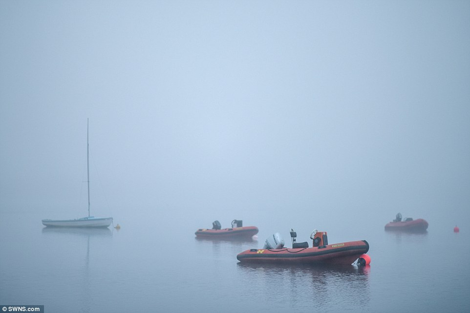 Spooky scene: Boats sit amongst thick fog on Loch Morlich near Aviemore in the Scottish Highlands this morning
