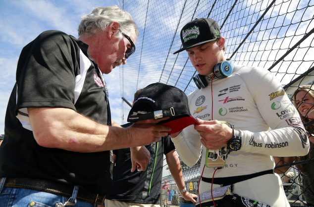 Sage Karam signs an autograph for a fan during the final practice session for the Indianapolis 500 auto race at Indianapolis Motor Speedway in Indianapolis, ...
