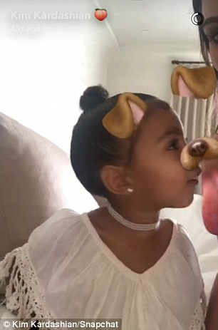 Getting into it: 'You're licking me!' Kim laughed as North got into character as a puppy